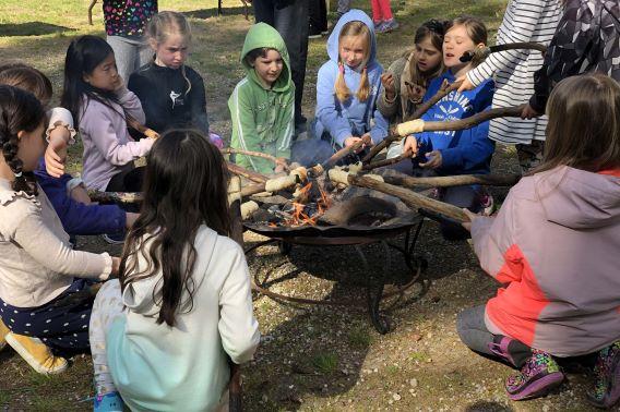 children cooking bannock around a campfire